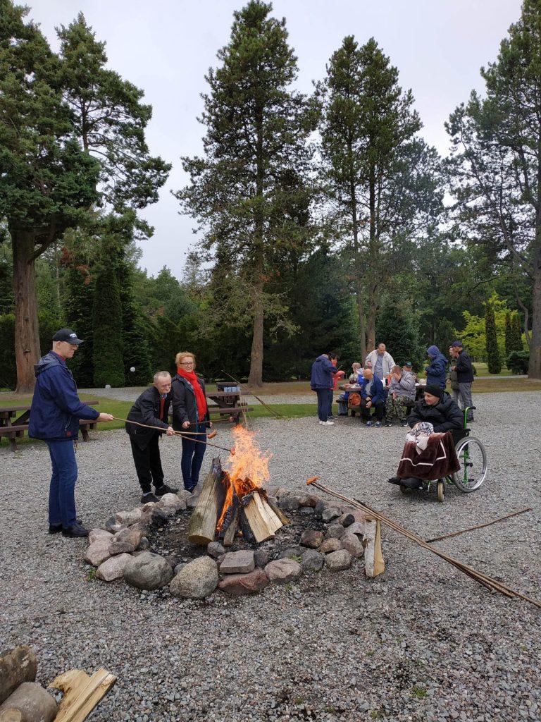 Smażenie kiełbasek przy ognisku w tle wszyscy uczestnicy, stół oraz piękne zielone drzewa w tle