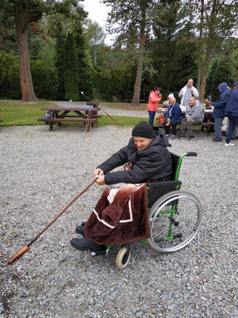 Mieszkaniec poruszający się na wózku smaży swoją kiełbaskę przy ognisku w tle jedzący przy stole mieszkańcy