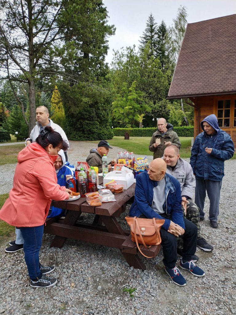 Mieszkańcy przy dużym drewnianym stole, opiekunka kroi kiełbaski, na stole soki i kiełbaski
