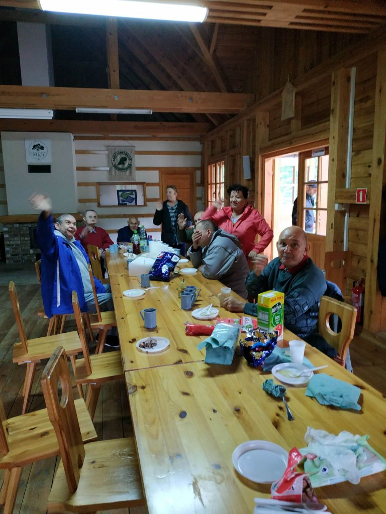 Machający mieszkańcy przy trzech dużych stołach w środku drewnianego budynku