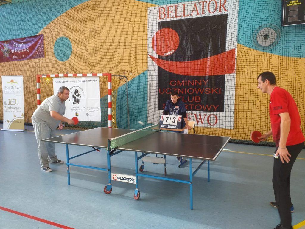Dwóch grających jeden w czerwonej koszulce drugi w siwej. Rozgrywają pojedynek na tablicy 1:0 oraz 7 do 3 dla przeciwnika DPS Rokocin.
