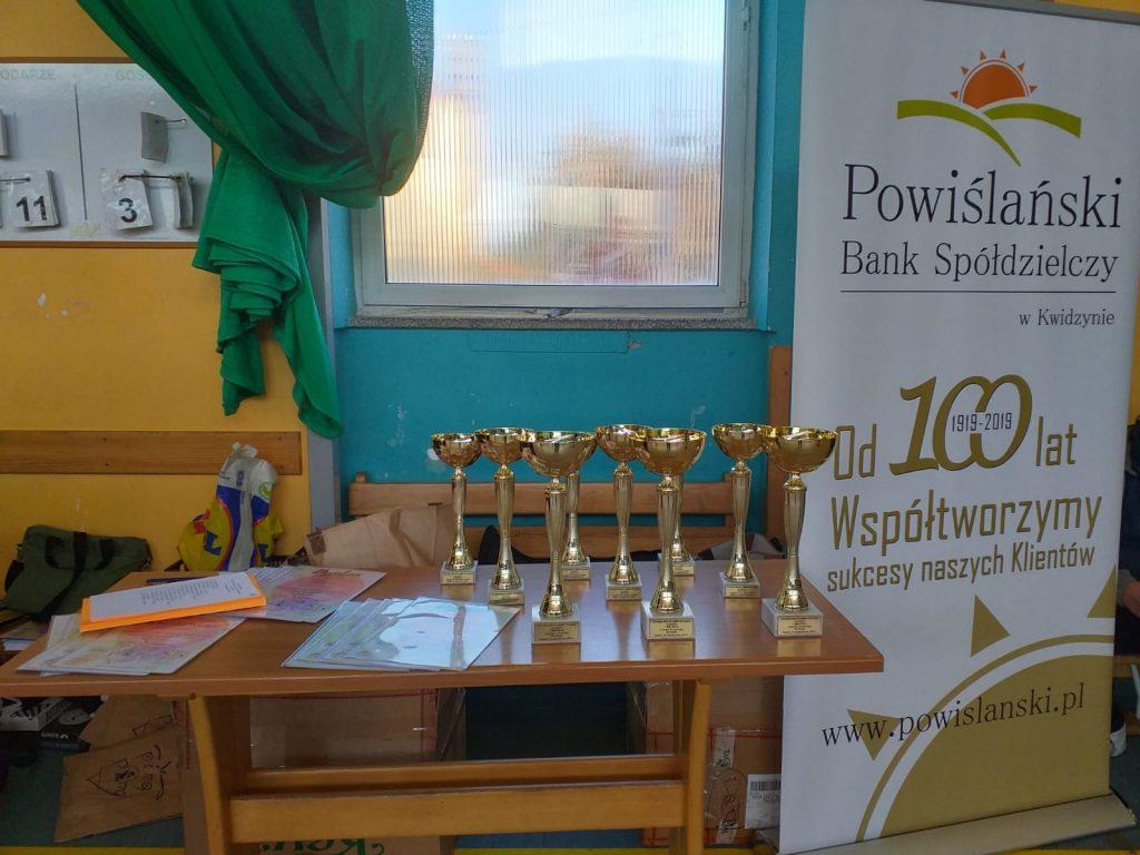Na drewnianym stole stoi 9 złotych pucharów przyznawane zwycięzcom swoich grup od 1 do 3 miejsca.