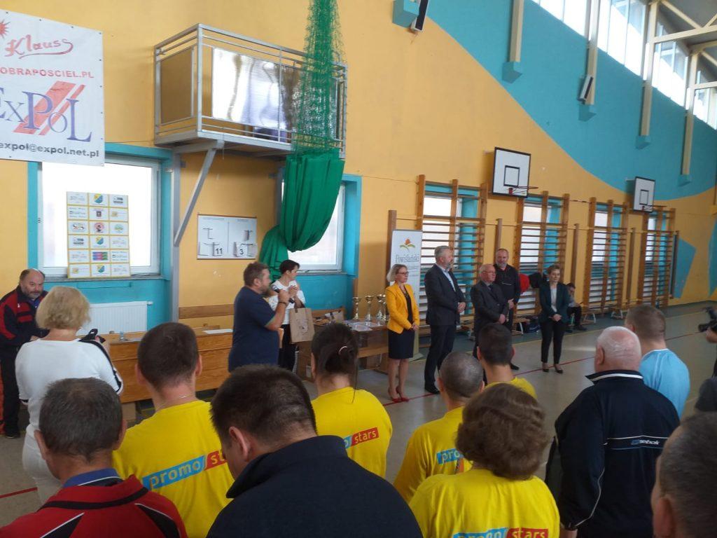 Jeden z sędziów stoi na środku z mikrofonem obok władze oraz w koło zebrani uczestnicy. Zakończenie turnieju.