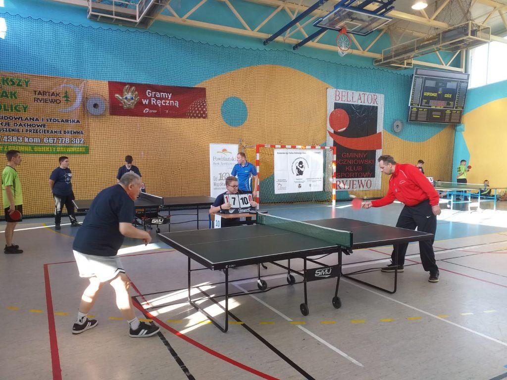 Dwóch grających jeden w czerwonej koszulce drugi w siwej. Rozgrywają pojedynek, na tablicy 1:0 oraz 7 do 10 dla naszego mieszkańca z DPS Rokocin. W tle inni gracze i sędzia