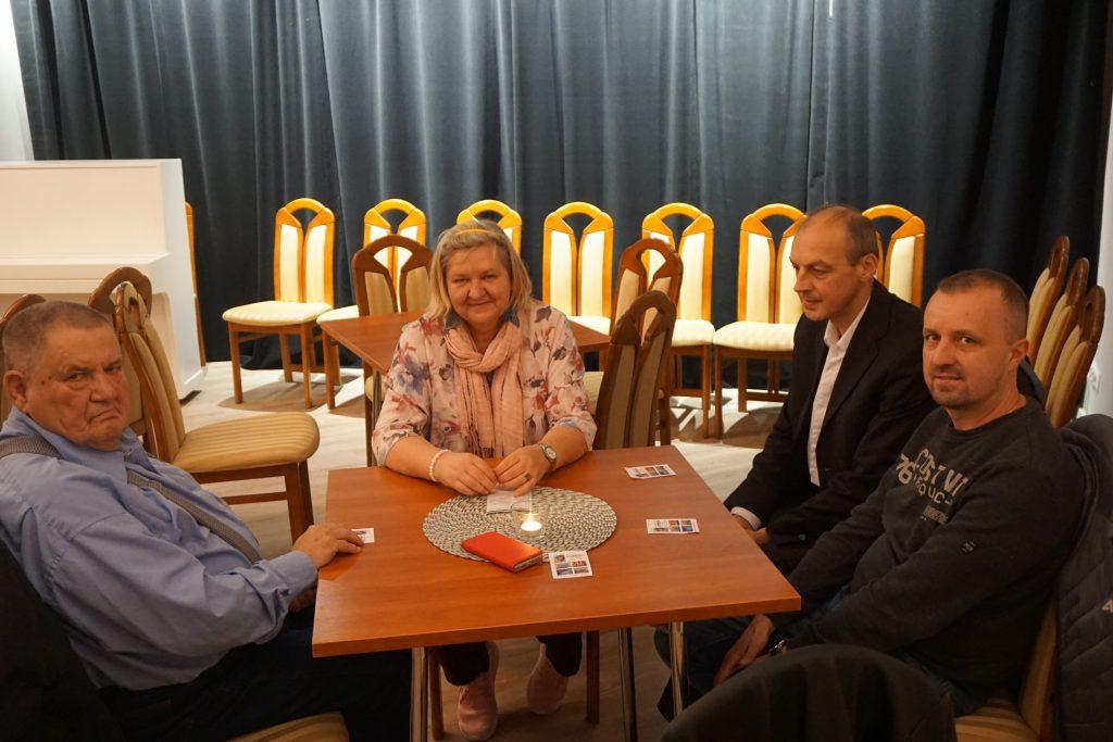 Cztery osoby siedzące przy drewnianym stoliku. W tle krzesła i białe pianino.