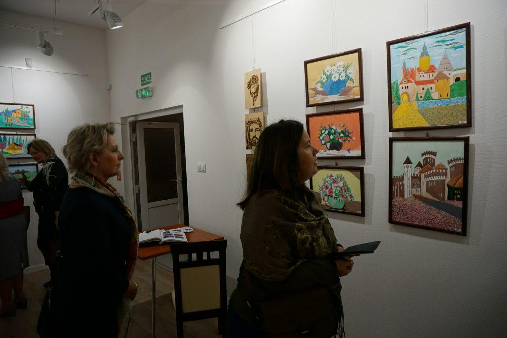 Dwie kobiety oglądające kolorowe obrazy podczas wystawy.