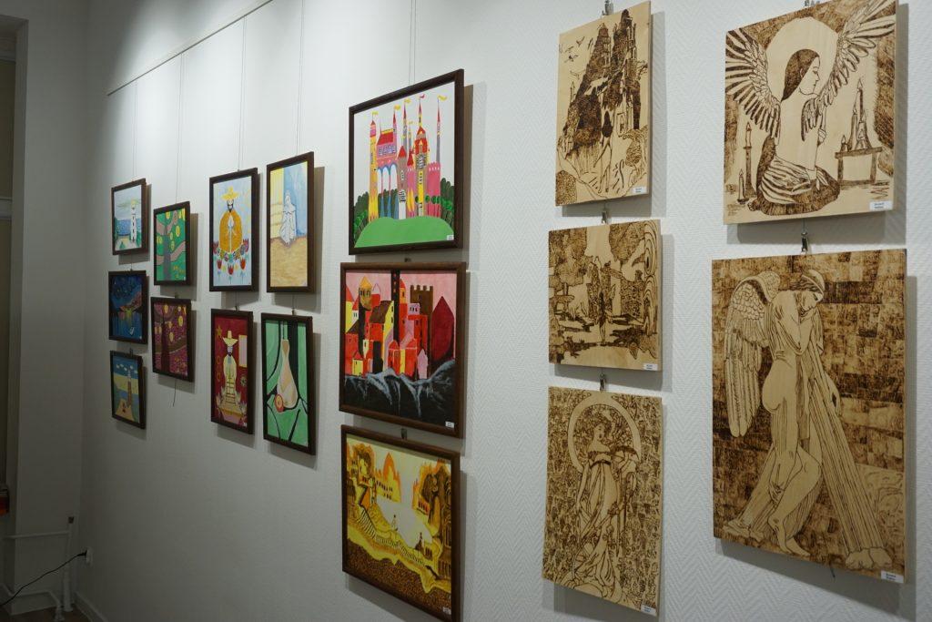 Kolorowe obrazy na płótnie oraz wypalanka w drewnie.