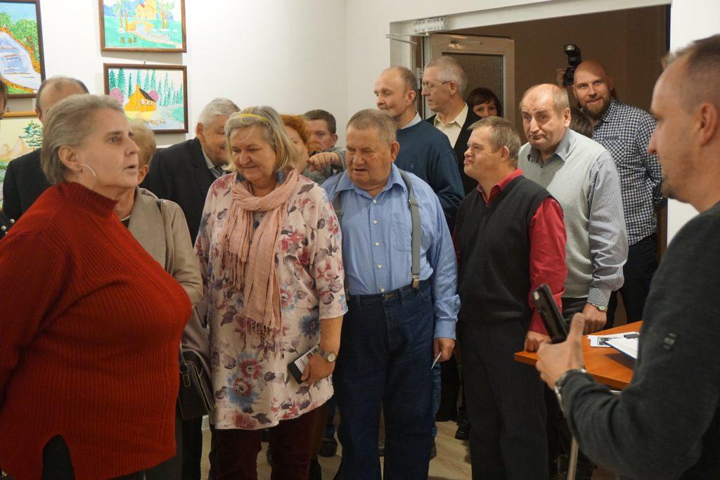 Grupa mieszkańców DPS oraz osób zainteresowanych wchodzących do pomieszczenia, gdzie odbywa się wystawa.