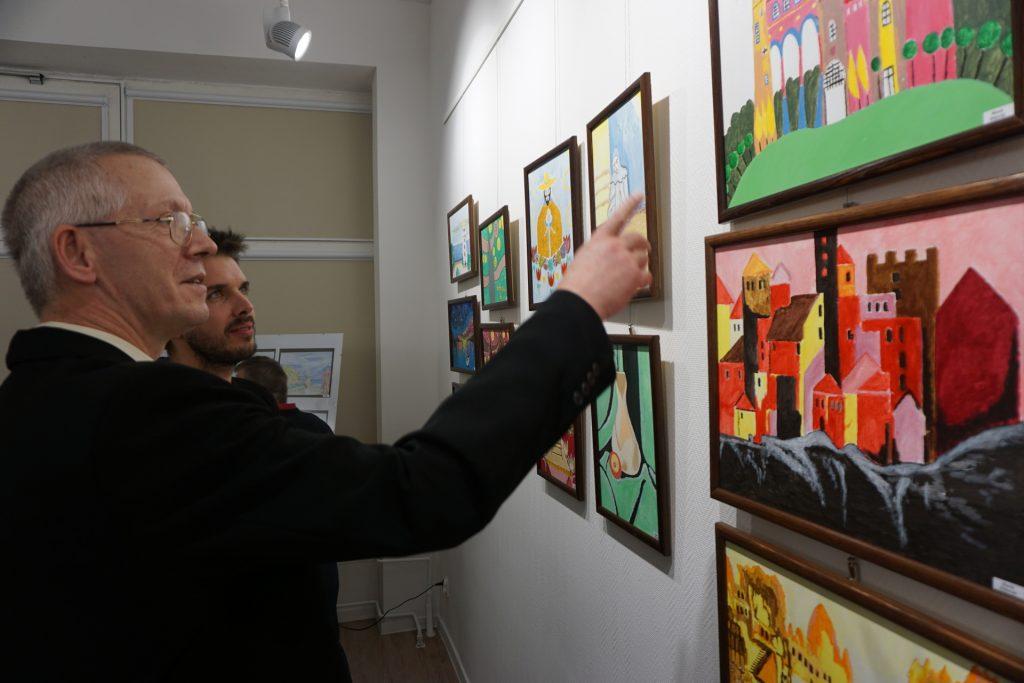 Jeden z artystów stojący przy obrazach i pokazujący palcem do gościa.