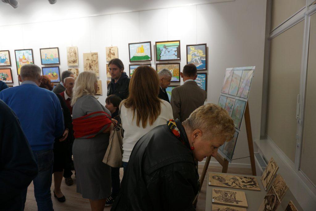 Grupa ludzi podczas wystawy w ODK. Oglądają obrazy.