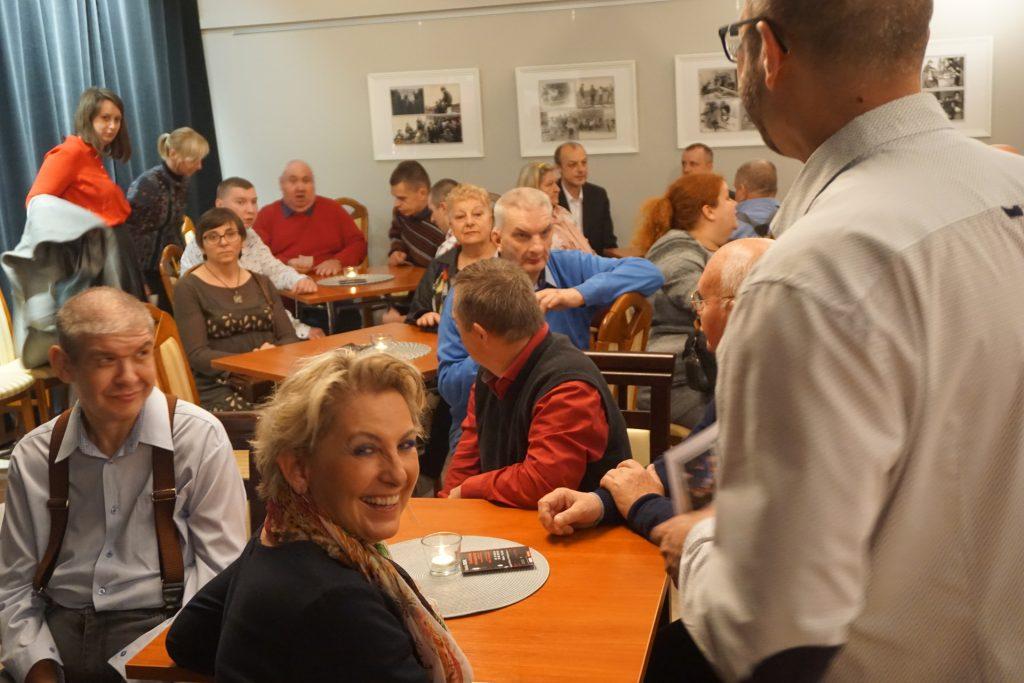 Grupa ludzi oczekująca rozpoczęcia wernisażu. Na pierwszym planie uśmiechnięta kobieta.