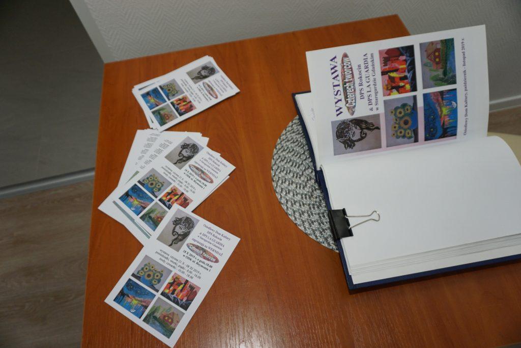 Księga wpisów leżąca na stole gdzie odbywała się wystawa. Obok niej ulotki wydarzenia