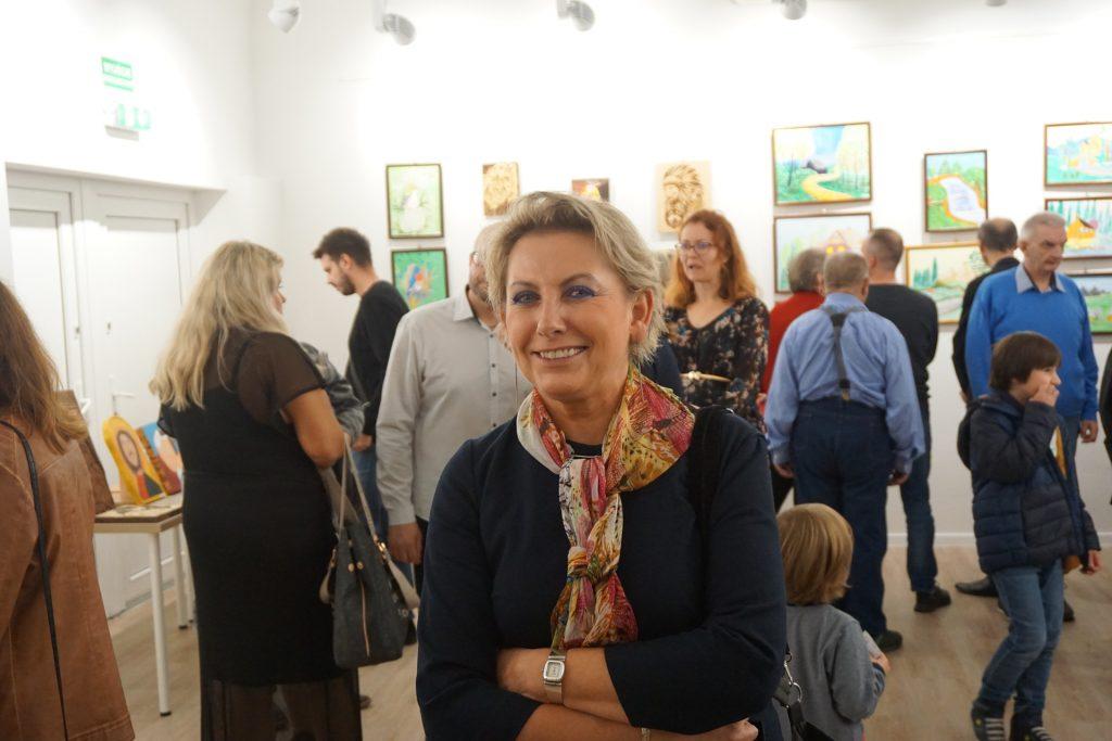 Kierownik DPS Rokocin uśmiechająca się do fotografa, który robi zdjęcie w tle goście.