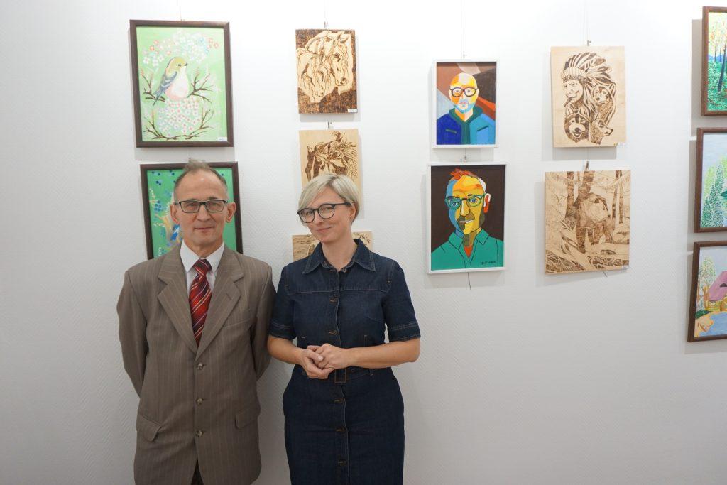 Zdzisław Tichonow jeden z artystów tego wydarzenia wraz z kierownikiem Osiedlowego Domu Kultury - Anną Karoliną Sprengel  pozują do zdjęcia na tle kolorowych obrazów oraz wypalanek.