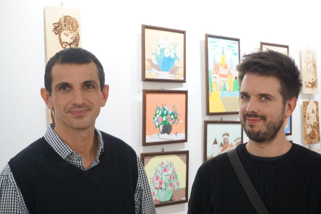 Dwóch mężczyzn uśmiechniętych i wpatrzonych w obiektyw osoby robiącej fotografię. W tle kolorowe obrazy