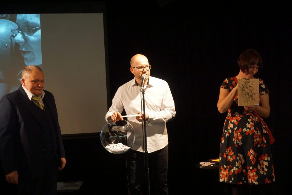 Trzy osoby stojące na scenie. Prowadzący Tomasz Bednarczyk trzyma w ręku kulę (losowa nagród) obok niego stoi jeden z artystów oraz Katarzyna Mokwa trzymająca obraz, który jest to wygrania