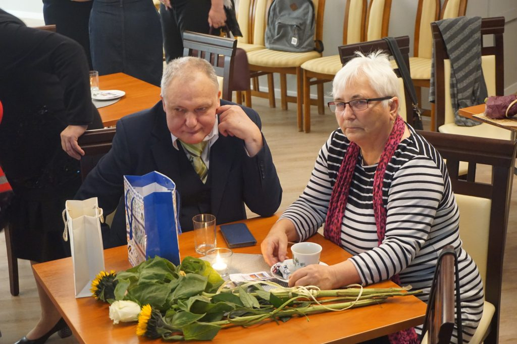 Artysta siedzący wraz z siostą przy stoliku. Na stole prezenty oraz kwiaty.