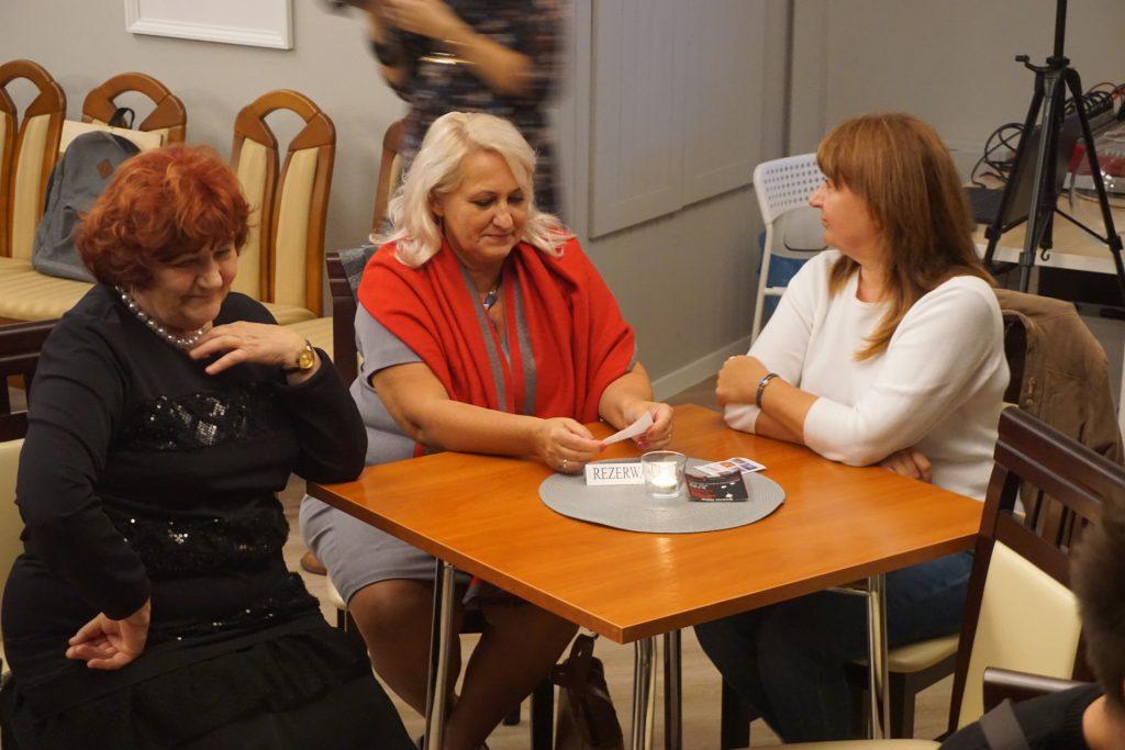 Dyrektorka Domu Pomocy Społecznej w Rokocinie siedząca przy stoliku z dwoma kobietami.