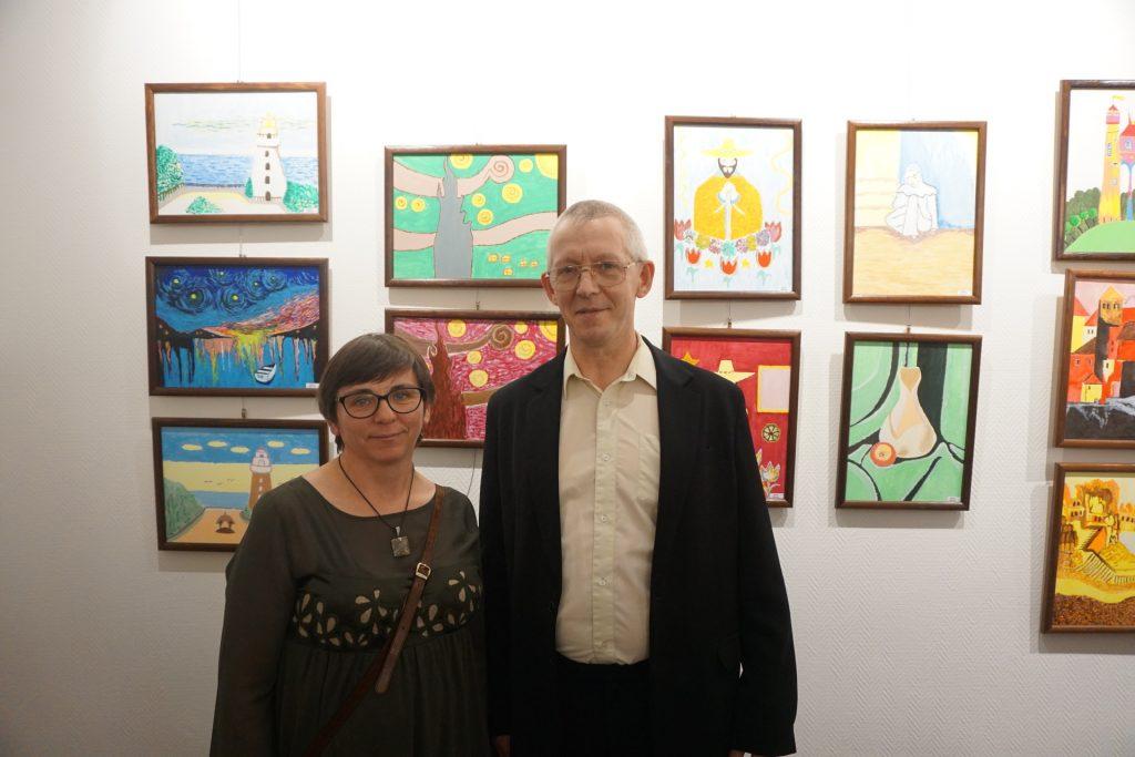 Artysta Marek wraz z siostrą na tle pięknych kolorowych obrazów.