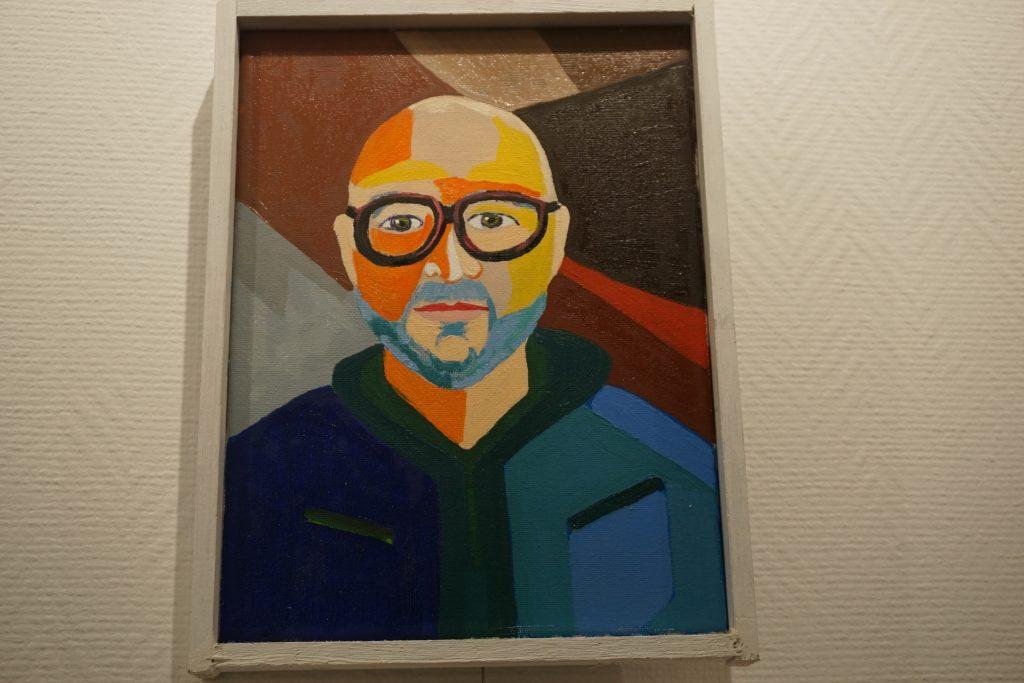 Kolorowy obraz, przedstawiający twarz jednego z artystów. Kolorowy autoportret