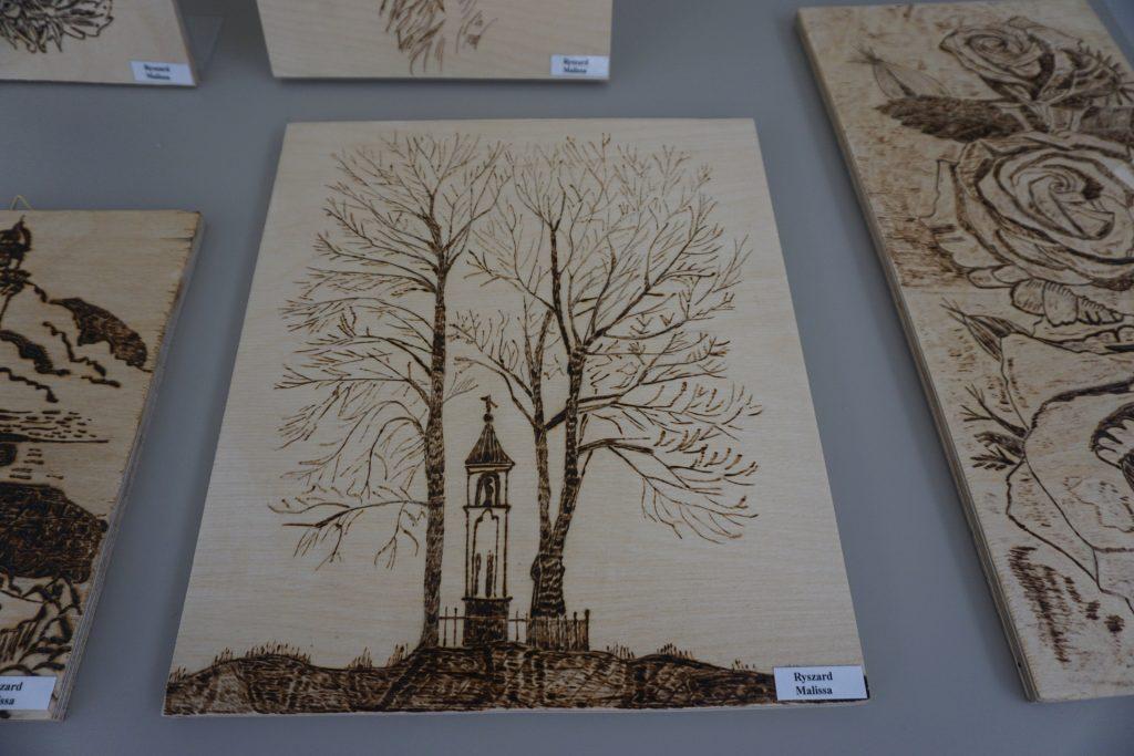 Zdjęcie obrazu - wypalanki autorstwa Ryszarda Mallisy. Na nim Kapliczka oraz dwa wysokie drzewa