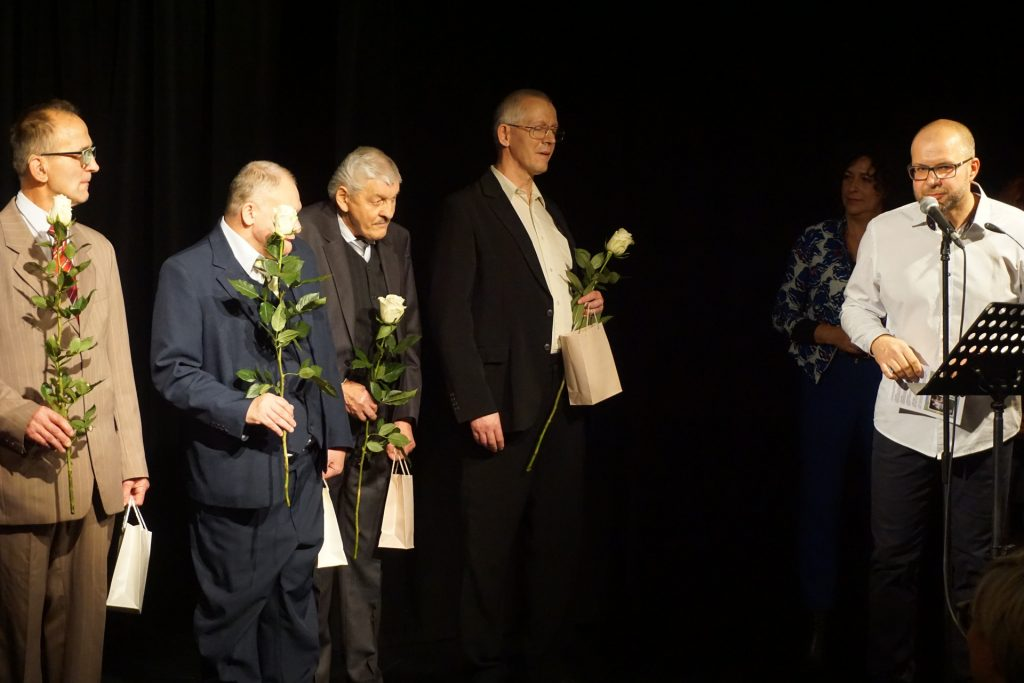 Czterech artystów trzymających róże. Przy mikrofonie prowadzący zapowiada artystów.