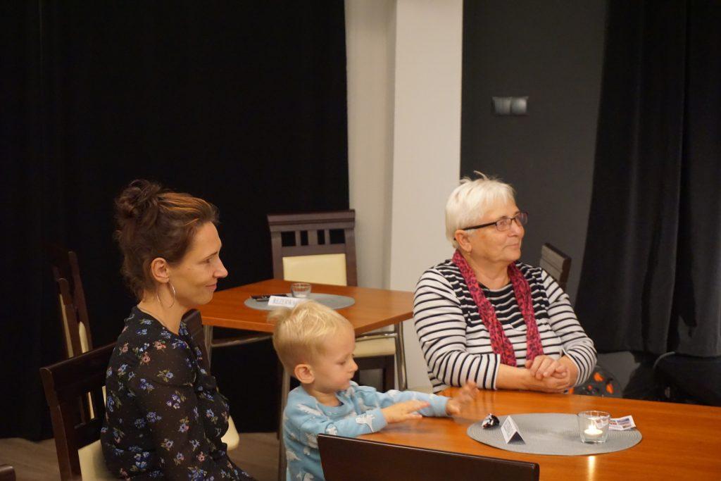 Dwie kobiety i dziecko patrzące w stronę sceny.