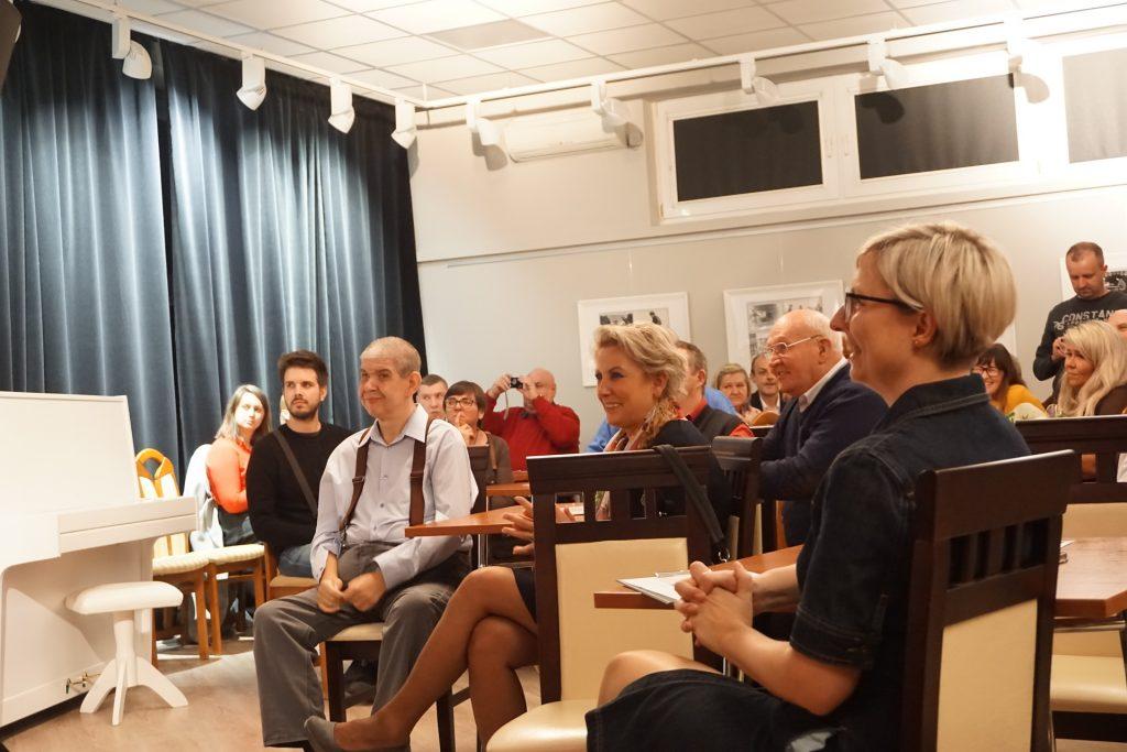 Grupa widzów, która przyszła na wernisaż. Siedzą na krzesłach i słuchają rozpoczęcia.