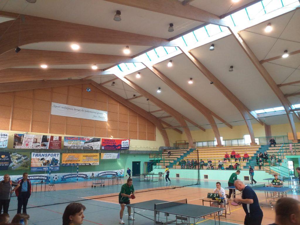 Zdjęcie hali sportowej, na hali stoły do grania w ping-ponga, trybuny, a na niej ludzie