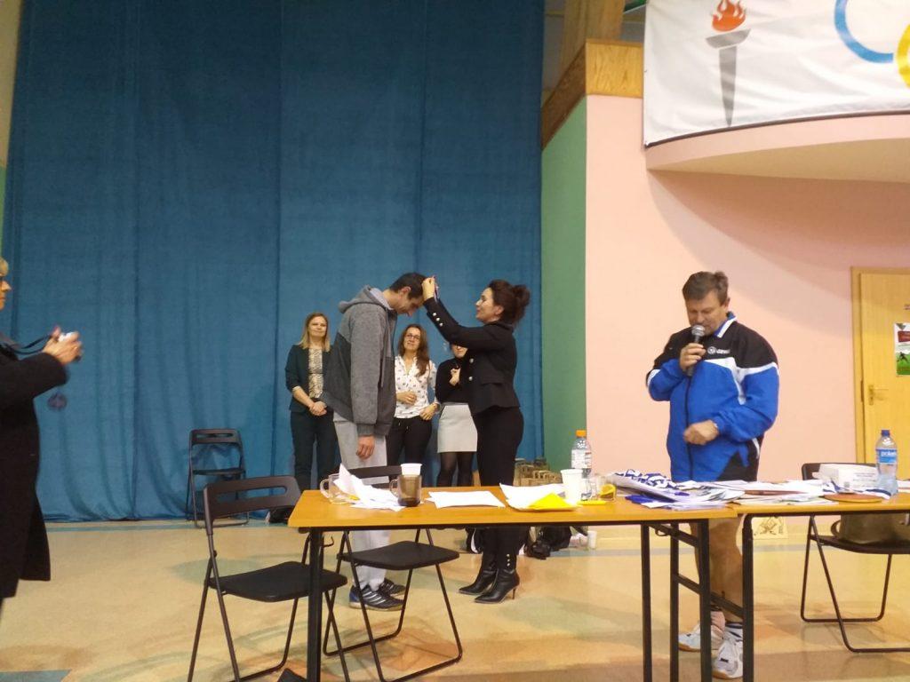 Jeden z podopiecznych DPS Rokocin podczas wręczania medali. Schyla głowę, aby nałożono mu złoty medal. W tle 3 kobiety obok jeden z sędziów trzymający mikrofon.