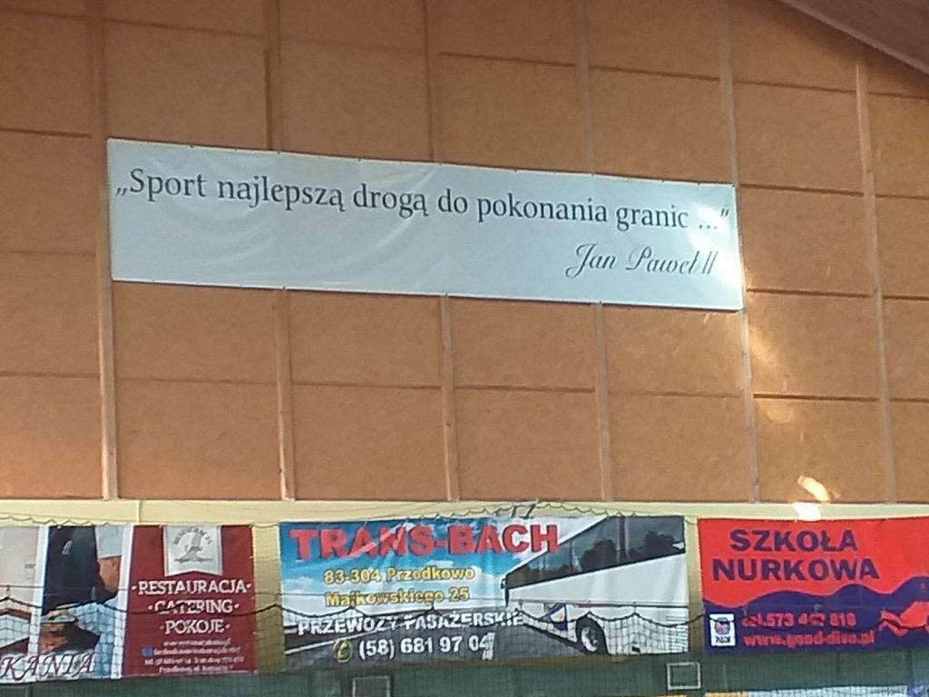 """Wielki baner na ścianie hali sportowej (Cytat Jana Pawła II) """"Sport najlepszą drogą do pokonania granic..."""""""