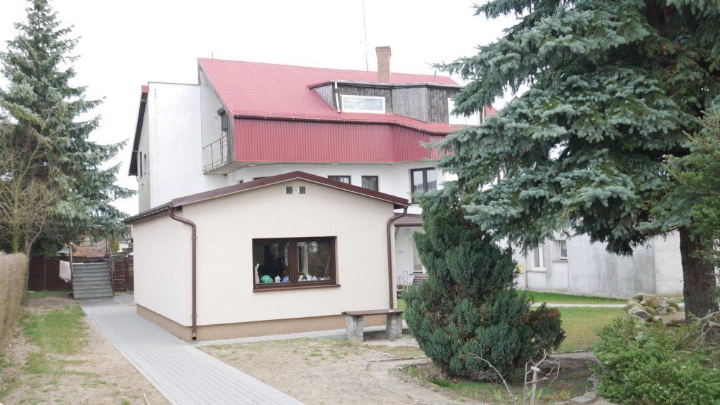 Duży dom piętrowy z balkonami oraz terenem zielonym na którym rosną wysokie choinki, drzewa i krzewy. Przy budynku znajduje się osobny budynek warsztatów terapii zajęciowej.