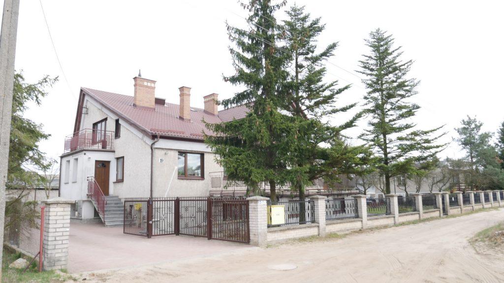 Duży domek piętrowy, otoczony sporym terenem. Na terenie rosną choinki.