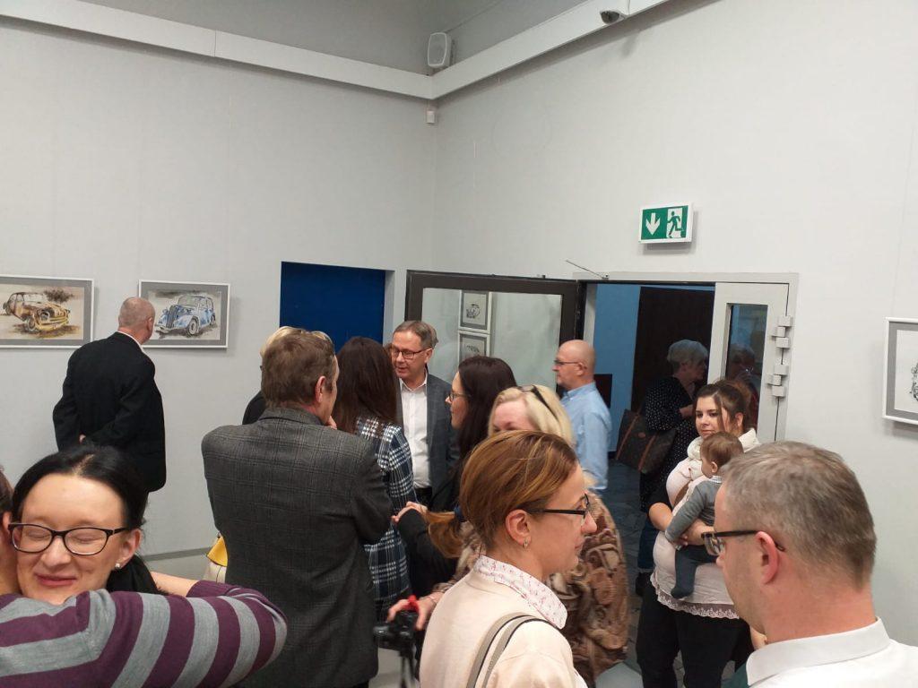 Grupa osób w tym prezydent Starogardu Gdańskiego rozglądających się po sali