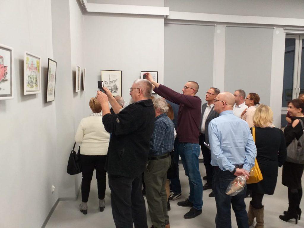 Tłum ludzi oglądających oraz robiących zdjęcia obrazom na ścianie.