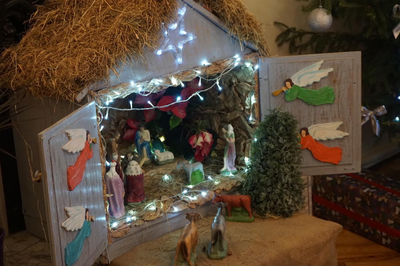 Drewniany żłobek ze zwierzątkami oraz aniołami na drzwiach stodoły