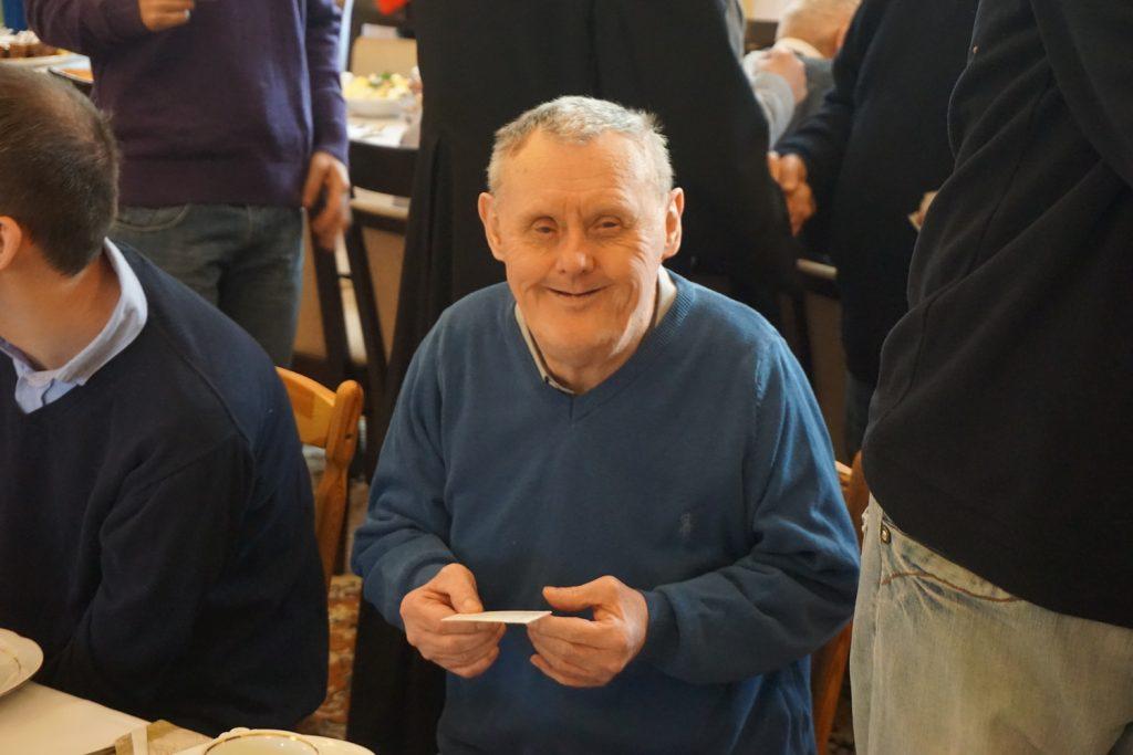 Podopieczny trzymający opłatek w ręku z uśmiechem na twarzy spogląda w obiektyw