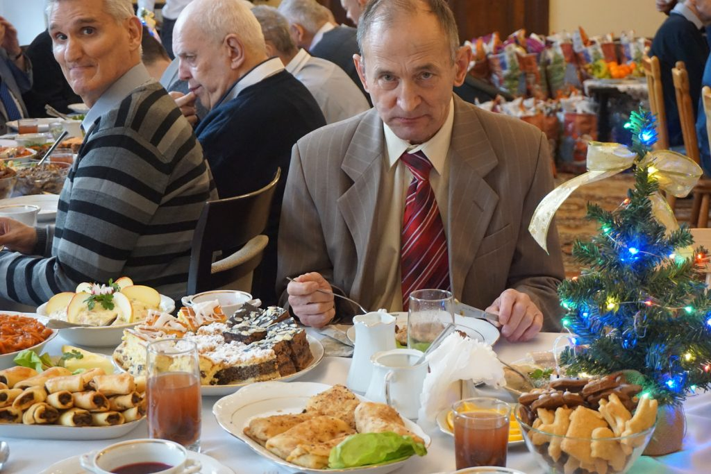 Mieszkaniec spoglądający w stronę obiektywu podczas konsumpcji ciasta, za nim kolejna osoba wpatrzona w stronę obiektywu
