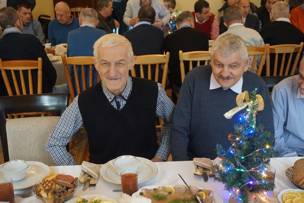 Dwóch mieszkańców przy stole patrzących w obiektyw. Uśmiechają się.
