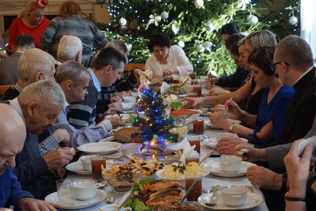 Syto zastawiony stół wigilijny oraz mieszkańcy i pracownicy siedzący przy nim