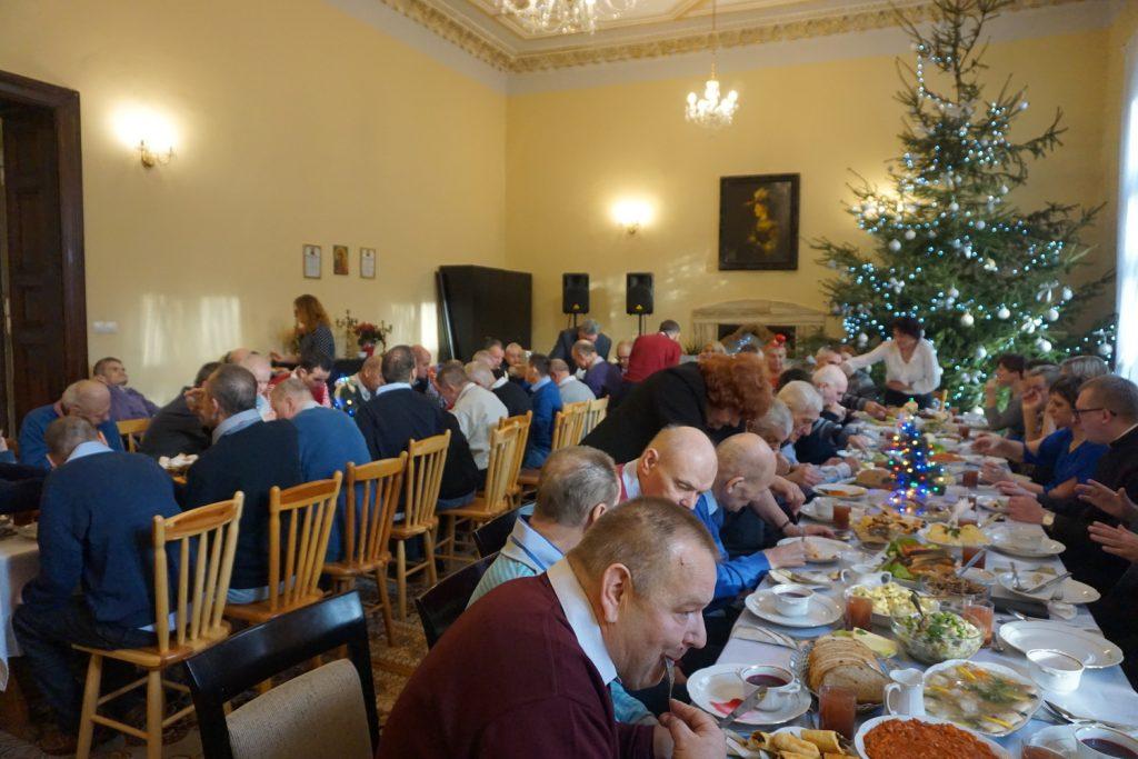 Ujęcie całej sali pełnej gości w tle zielona pięknie ustrojona choinka