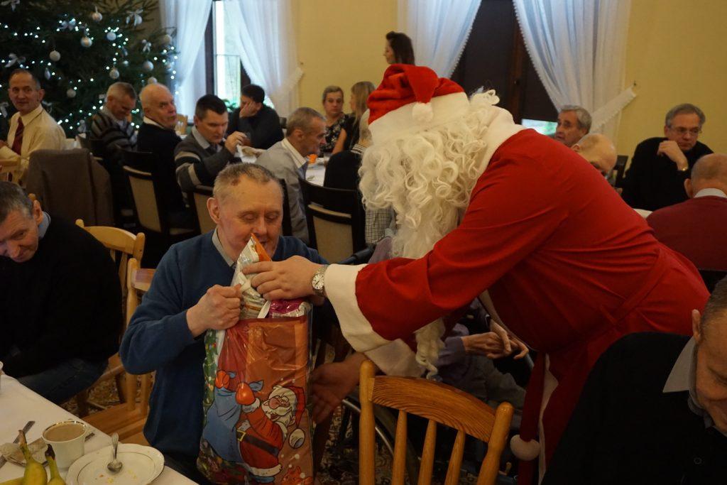 Św Mikołaj wręcza świąteczną paczkę mieszkańcowi siedzącemu przy stole wigilijnym