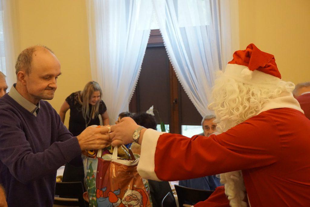 Św Mikołaj wręczający paczkę mieszkańcowi