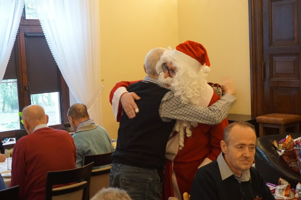 Św Mikołaj podczas rozdawania paczek obściskując się z mieszkańcem