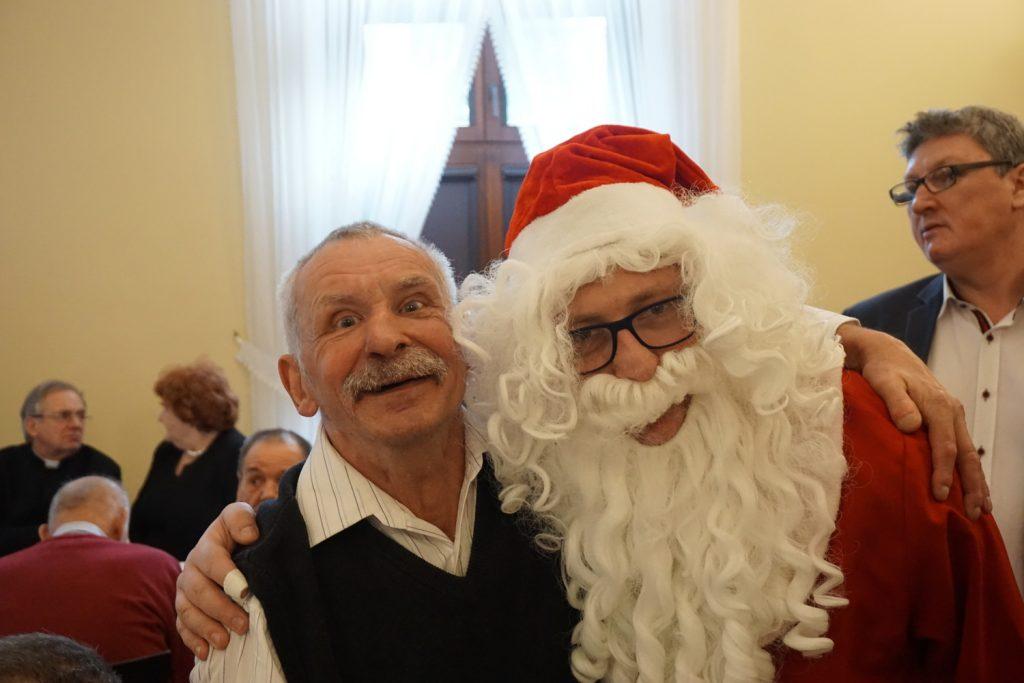 Uśmiechnięty podopieczny domu wraz z Św Mikołajem spoglądają w stronę obiektywu