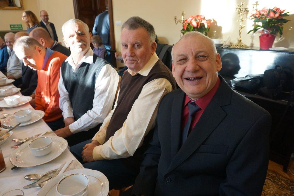 Mieszkańcy przy stole, na pierwszym planie uśmiechnięty podopieczny