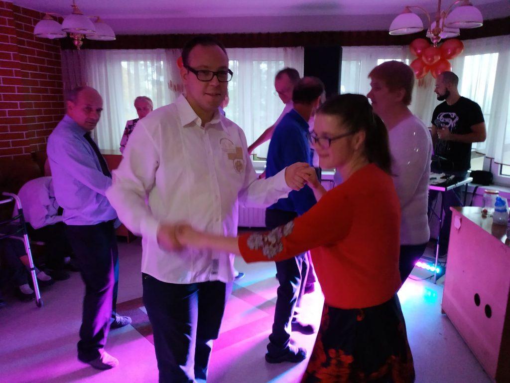 Para osób trzymająca się za ręce, tańczą. W tle inni uczestnicy zabawy.
