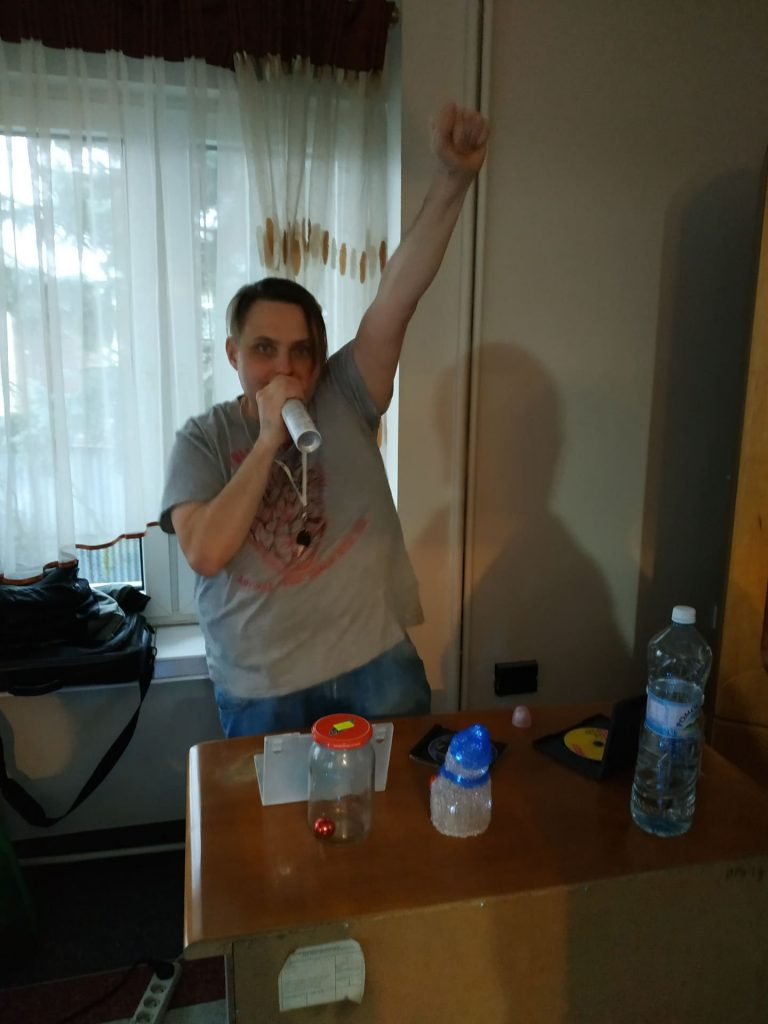 Mieszkaniec trzymający w ręku dezodorant , śpiewający, druga ręka uniesiona ku górze.