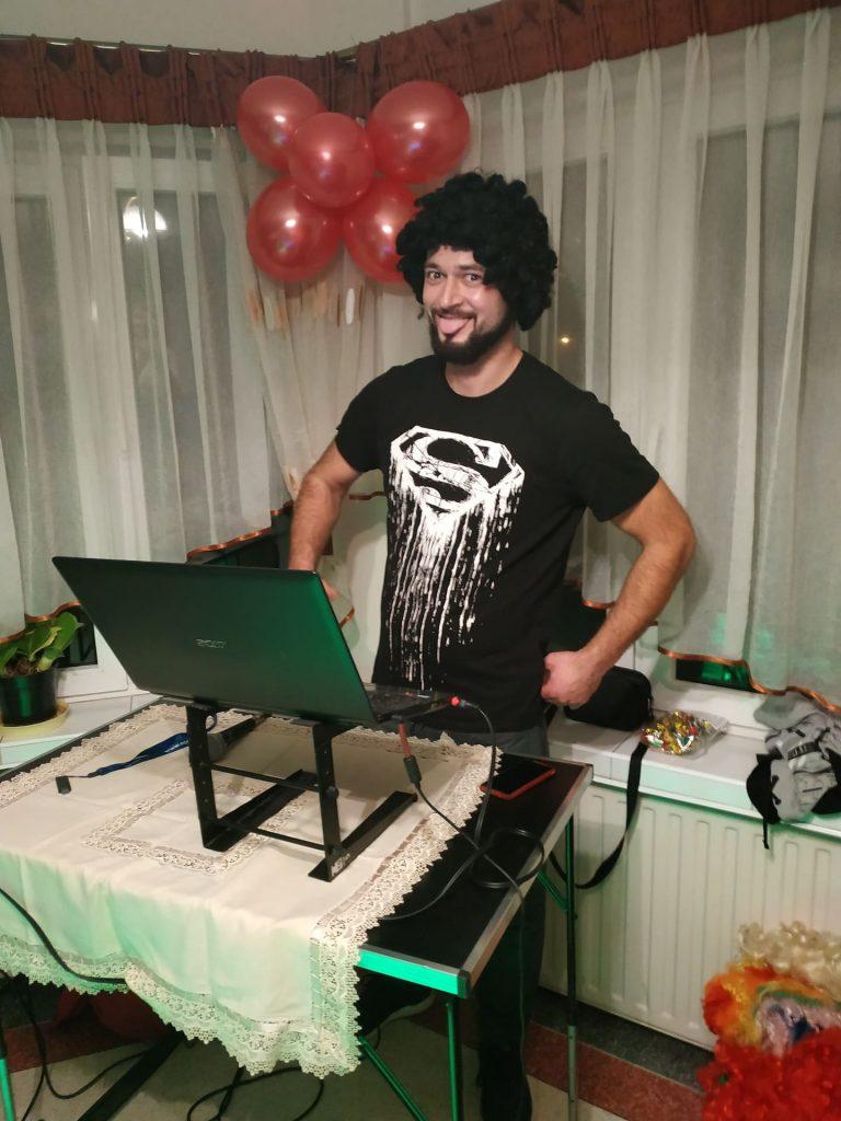 DJ za stanowiskiem muzycznym podczas puszczania utworów na głowie ma czarną perukę.