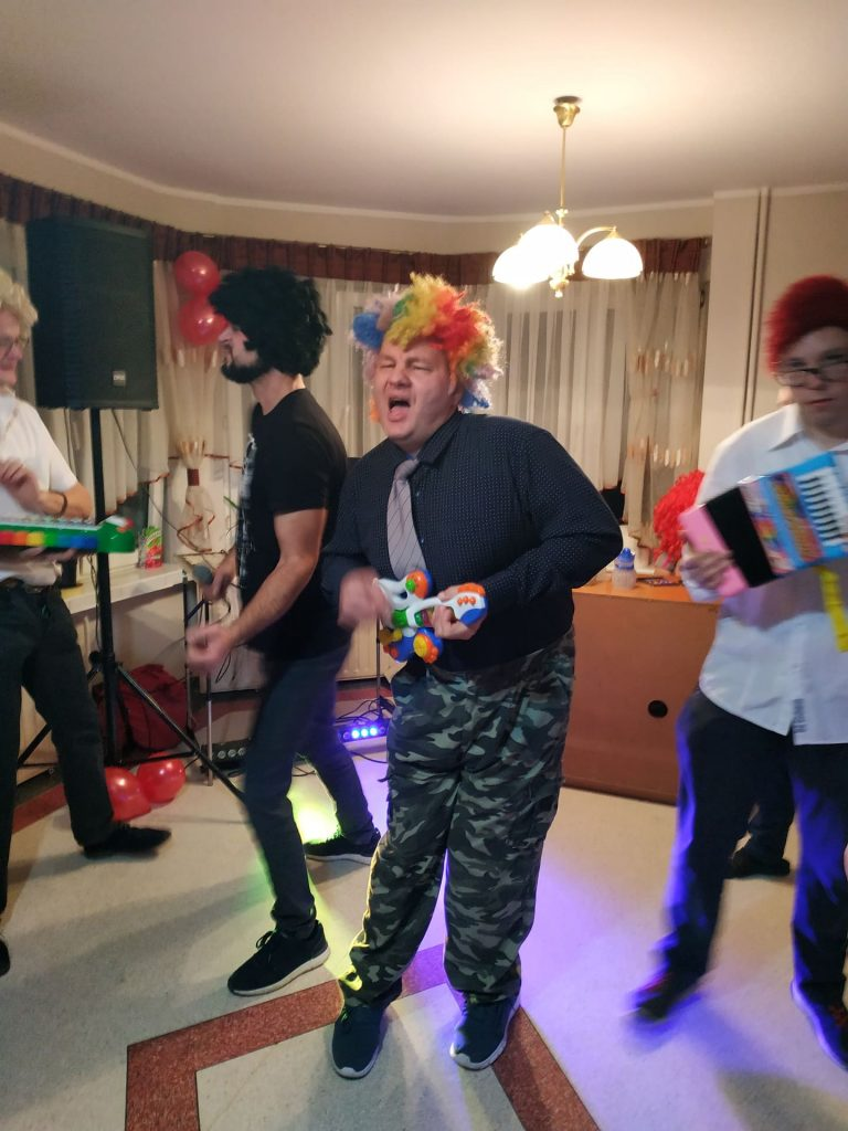 Grupa osób udająca, że grają utwór na zabawkach typu gitara, akordeon oraz cymbałki. Wraz z nimi DJ. Jeden z mieszkańców trzymający kolorową gitarę śpiewa.